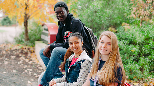 Students sitting on a bench on campus on a Fall day