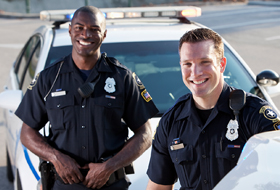 Two police officers standing near parked car