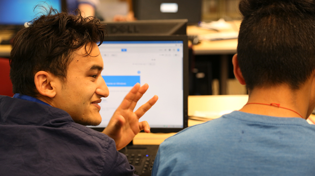 Two students discussing project in front of computer in the Wright Library
