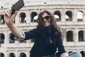 Female student taking a selfie in front of Colosseum
