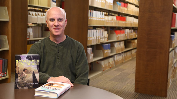 Professor Dr. Joshua Bellin poses with his two science fiction novels in the Wright Library at La Roche College.