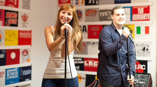 Two students singing on stage in the Bold Hall Union Room