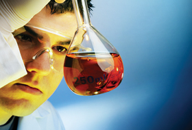 Male science student examining liquid in test tube.